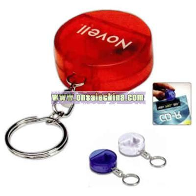 Round CD opener with key holder attached